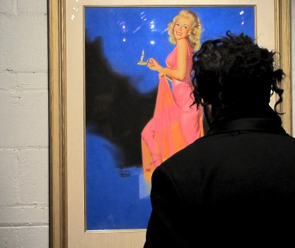 A man in black admires a lady in pink (Earl Moran's The Chamber Maid).