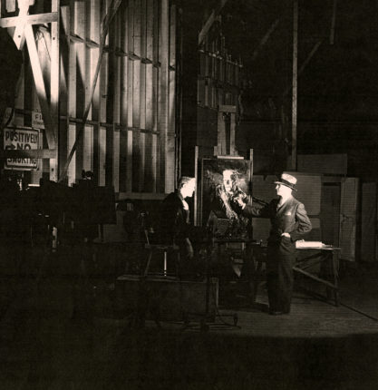 The artist Rolf Armstrong painting Boris Karloff as Frankenstein