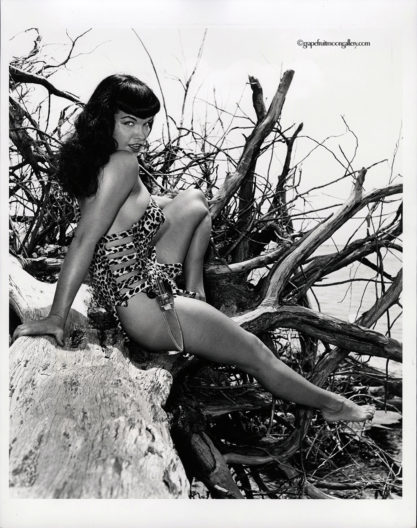 Bettie Page with Knife Seated on Driftwood - Full View