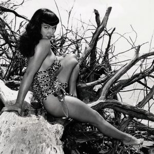 Bettie Page with Knife Seated on Driftwood