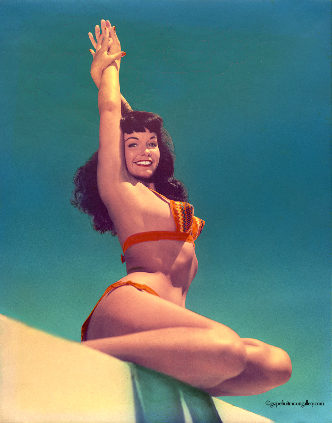 Bettie Page smiling with hands overhead