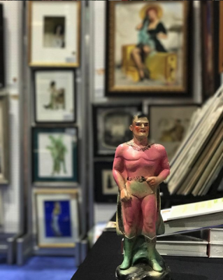Chalkware Superman in front of pin up paintings