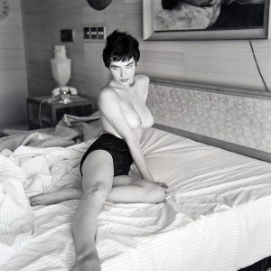 Pin-up model Dondi Penn photographed topless and posed on a bed